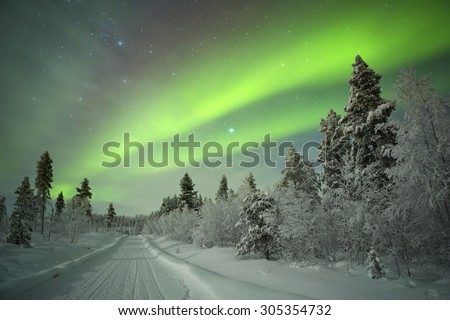 Spectacular aurora borealis (northern lights) over a track through winter landscape in Finnish Lapland. - stock photo