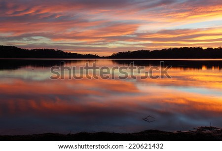 Spectacular cloud reflections on Narrabeen Lakes at sunrise. - stock photo