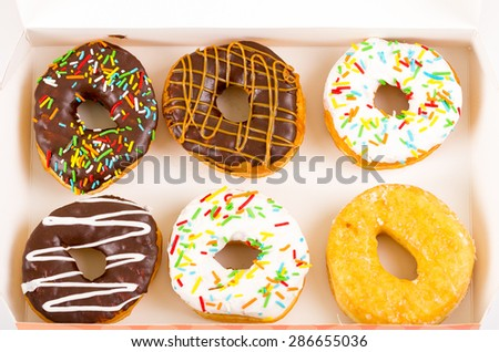 spectacular display of 6 donuts of various flavours such as chocolate and vanilla in box - stock photo