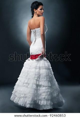 Spectacular fashion model brunette girl in wedding dress posing on podium - stock photo