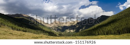 Spectacular Rocky Mountain panoramic view of the Gore Range near Vail, Colorado with blue sky and billowing clouds. - stock photo