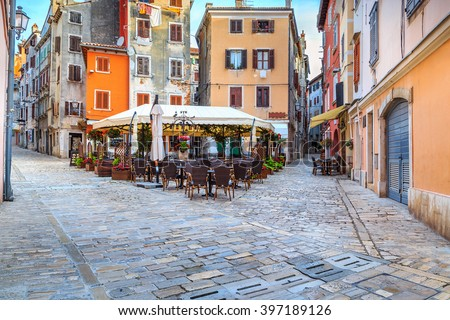 Spectacular stone paved street with colorful houses and typical street cafe bar, Rovinj old town,Istria region,Croatia,Europe - stock photo