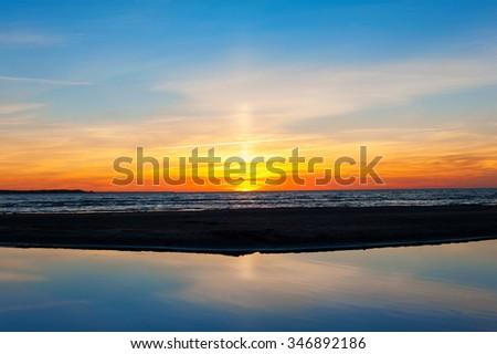 Spectacular summertime sunset on Baltic sea beach. Blue sky background. Horizontal outdoors image - stock photo