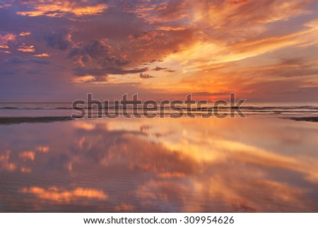Spectacular sunset colours over sea reflected in the water at low tide. Photographed on the island of Texel, The Netherlands. - stock photo