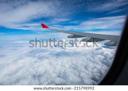 Spectacular view from  an airplane's window, offering a view of lovely clouds and blue sky while traveling fast