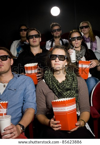 Spectators with popcorn at the movie theater - stock photo