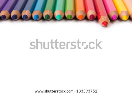 Spectrum of color pencils with the focus on red pencil - stock photo
