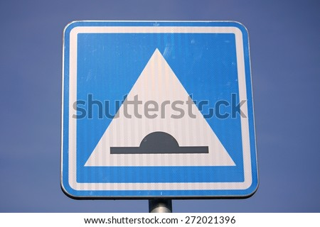 Speed bump road sign against blue sky - stock photo