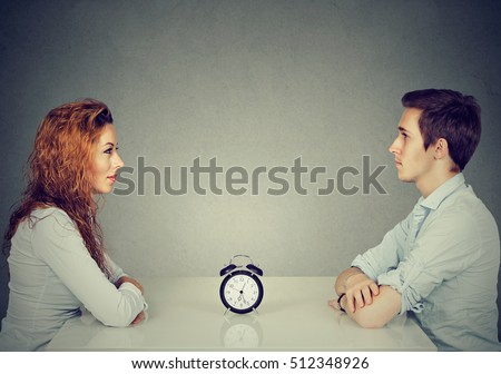 Speed dating. Man and woman sitting across from each other at table with alarm clock in-between