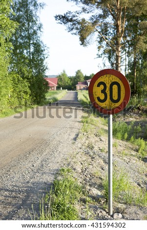 Speed limit sign in the country side on a summer evening. The speed limit is 30 km/h on a gravel road. The focus point is on the speed limit sign on the right.