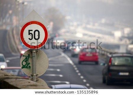 Speed limit traffic sign on a busy urban road - stock photo