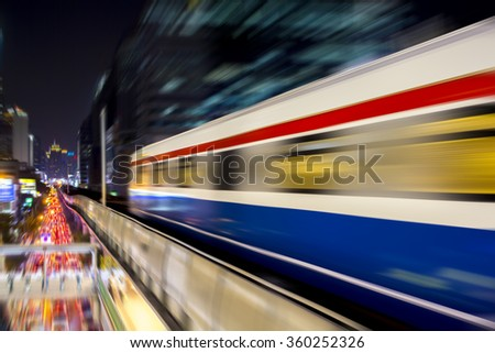 Speed motion Blur from Sky Train at night in modern city (background) - stock photo