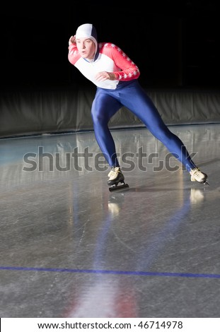 Speed skater accellerating towards the finish line of a long distance race on an ice rink - stock photo