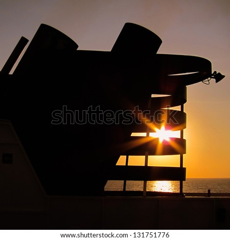 Speedboat chimney against the sun - stock photo