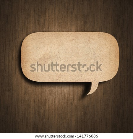 speedch bubble paper on wood background - stock photo