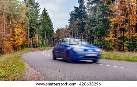 Speeding car blurred on road through colorful autumn trees