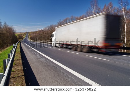 Speeding motion blur white truck on empty asphalt road in a rural landscape. Sunny day with blue skies. - stock photo