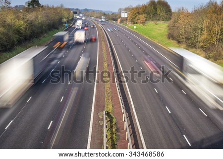 Speeding traffic on an English motorway with long exposure for motion blur - stock photo