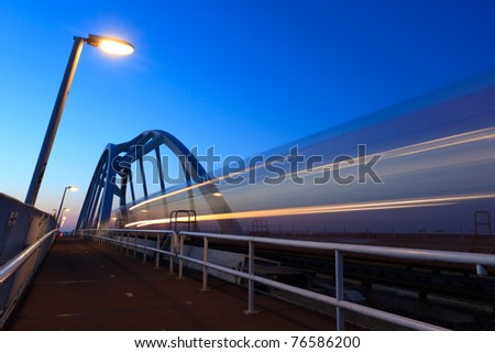 Speeding train, with motion blur, on a bridge at dusk. - stock photo
