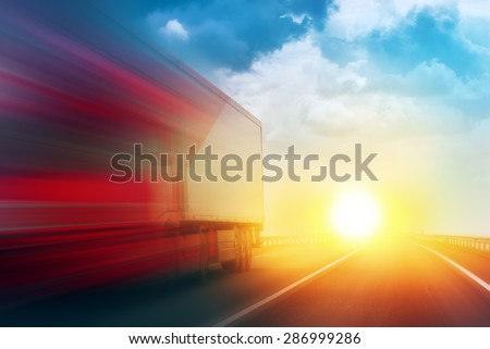 Speeding Transportation Delivery Truck on Open Highway with Sun Setting Down on Horizon in Background. - stock photo