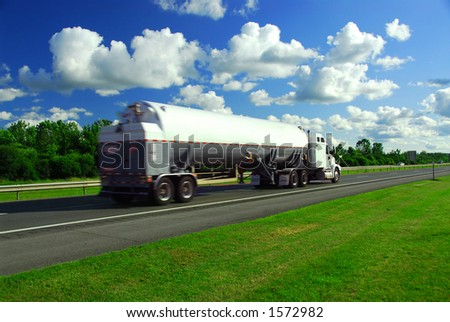 Speeding truck delivering gasoline on highway blurred because of motion - stock photo