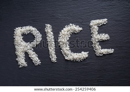 spelling out the word rice on black slate serving board                                - stock photo