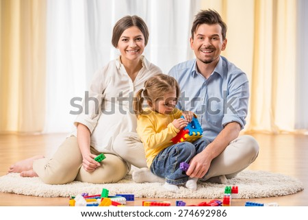Spend time relaxing together. Happy pregnant mother and young father is playing with daughter. - stock photo