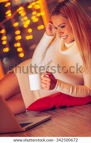 Spending good time at home. Beautiful young woman in white sweater and socks looking at laptop and drinking hot drink while lying on the floor at home with Christmas lights in the background - stock photo
