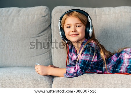 Spending great time at home. Beautiful little girl in headphones looking at camera with smile while lying on front on the couch at home - stock photo