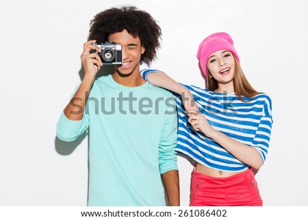 Spending great time together. Funky young couple smiling while standing against white background - stock photo