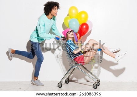 Spending great time together. Happy young man carrying his beautiful girlfriend in shopping cart and smiling while running against grey background - stock photo