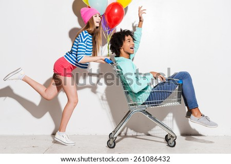 Spending great time together. Happy young women carrying his boyfriend in shopping cart and smiling while running against grey background - stock photo