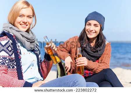 Spending great time together. Two beautiful young women holding beer bottles and smiling while sitting on the beach together - stock photo