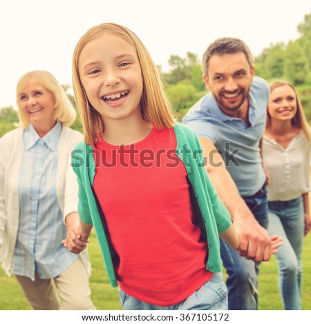 Spending great time with family. Happy little girl enjoying time with her family while walking outdoors together - stock photo