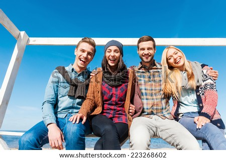 Spending great time with friends. Low angle view of four happy young people bonding to each other and smiling while sitting at the riverbank - stock photo