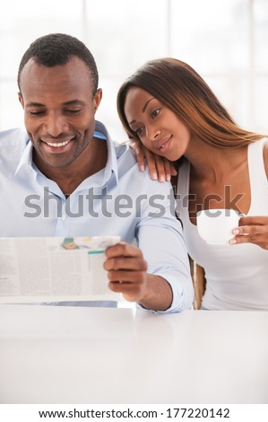 Spending morning time together. Beautiful young African couple sitting together and reading newspaper while woman leaning at shoulder of her husband - stock photo