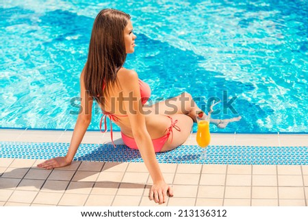 Spending summer time poolside. Rear view of young woman in bikini sitting by the poolside with cocktail near her - stock photo