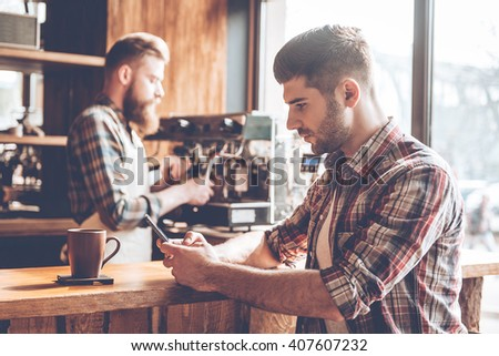 Spending time at coffee shop. Side view of young handsome man using his smartphone while sitting at bar counter at cafe with barista at the background - stock photo