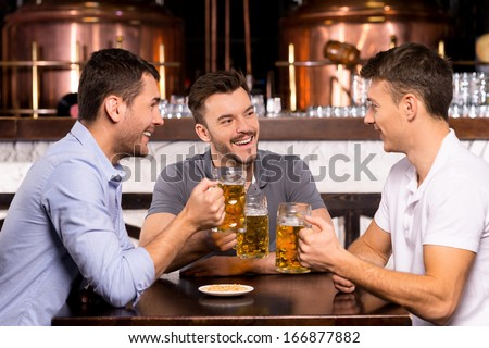 Spending time in bar. Three cheerful friends drinking beer in bar - stock photo