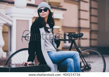 Spending time outdoors.  Side view of beautiful young woman in sunglasses holding coffee cup and looking away while sitting on bench outdoors  - stock photo