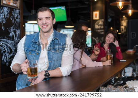 Spending time with beer. Portrait of young handsome man who is standing in a pub with glass of beer and smiling. His friends are standing on the background