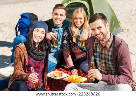 Spending time with friends. Group of young cheerful people drinking beer and talking while camping at the riverbank  - stock photo