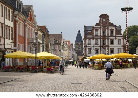 Speyer, Germany - May 2, 2014: People walk and cycle in the mainstreet flanked with historical buildings, shops and the old clocktower in the old centre of Speyer, Germany on May 2, 2014 - stock photo