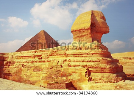 Sphinx statue and pyramid of Cheops on the background. Giza plateau in Egypt - stock photo