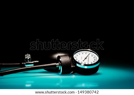 Sphygmomanometer on blue, reflective table and black background - stock photo
