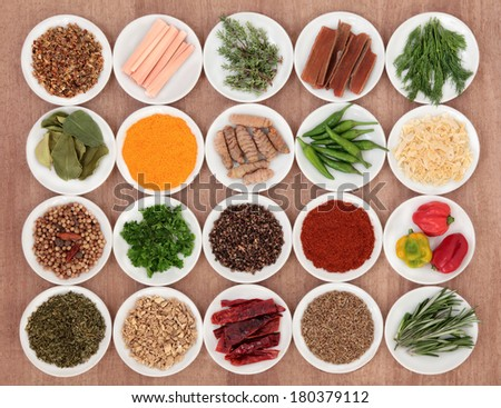 Spice and herb selection in china bowls over papyrus paper background.