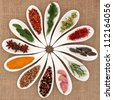 Spice and herb selection in white porcelain dishes over hessian background. - stock photo