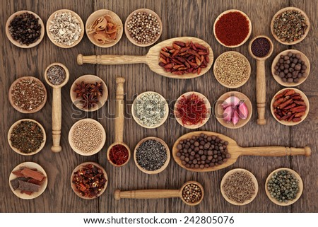 Spice and herb selection in wooden bowls and spoons over old oak wood background. - stock photo