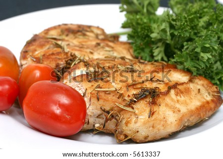Spice baked chicken breast meat with cherry tomatoes and parsley - stock photo