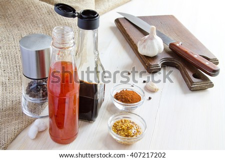 Spice. Chili, pepper, soy sauce, knife and cutting board - stock photo